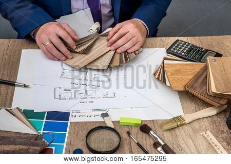 Man architect draws a house plan with color palette for furniture work tools.