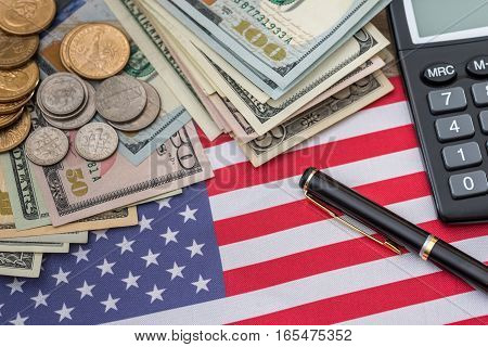 business concept - us flag dollar banknotes us cent coin pen and calculator.