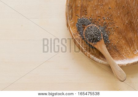 Chia seeds on wooden background, top view.