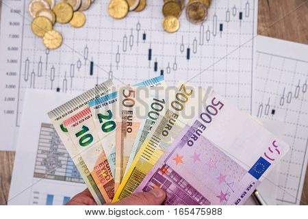 Euro currency on paper background with chart.