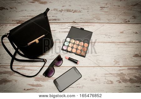 Little black ladies handbag eye shadow sunglasses phone and lipstick on wooden background. Fashion concept. Top view space for text