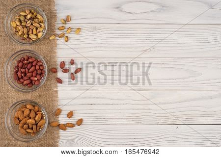 Mix nuts in a glass bowl on the old wooden table. Top view.
