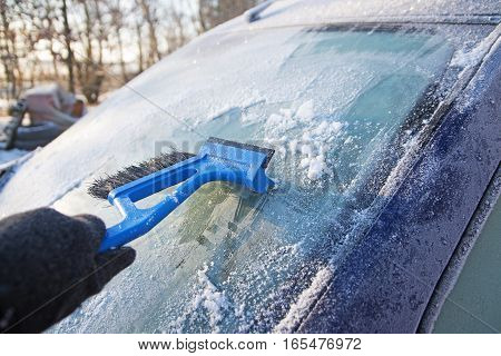Frozen windshield from a car and a hand scraping the ice with an ice scraper preparation for winter driving selected focus narrow depth of field
