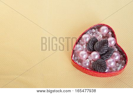 Heart Pink Pearls And Chocolate Leaves On A Yellow Background