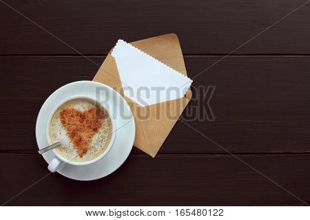 heart symbol of frothy cappuccino cinnamon in the background of open envelope to the wishes / flavor warming feeling