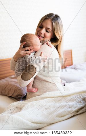 Beautiful young mother holding her baby son in her arms, sitting on bed