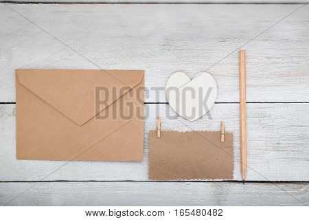 envelope kraft paper and white wooden heart on a white wooden background. View from above