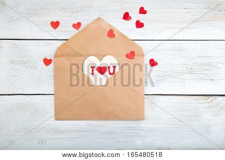 Valentine. envelope kraft paper and red hearts on a wooden background. View from above