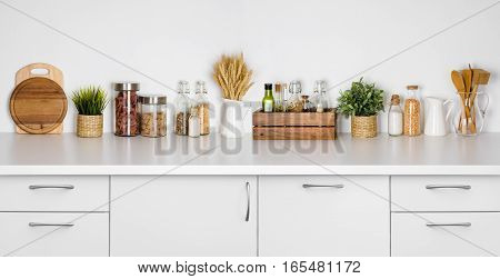 Kitchen bench shelf with various herbs spices utensils on white