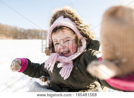 Cute little girl in green jacket and knitted hat an gloves playing outside in winter nature