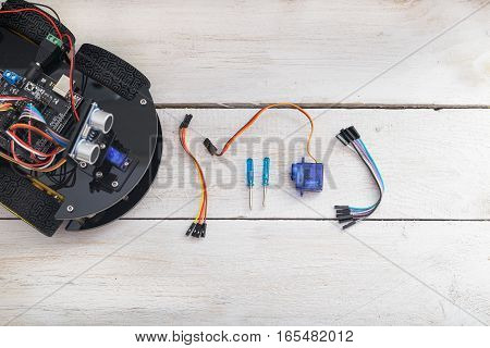 robot elements. Servo screwdriver lying on a wooden table. view from above