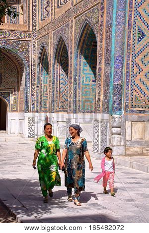SAMARKAND, UZBEKISTAN - MAY 17, 2011: Two Uzbek women and a little girl walking in the courtyard of a madrasa at the Registan