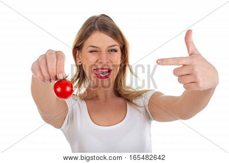 Picture of a funny young woman holding a cherry tomato