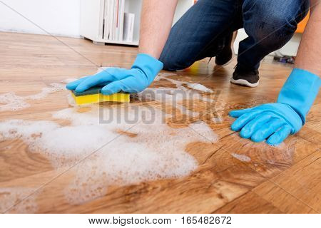 Cleaning A Parquet Floor With Foam On The Floor