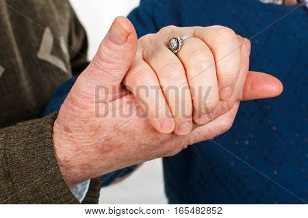 Close up picture of an old couple's hand holding each other