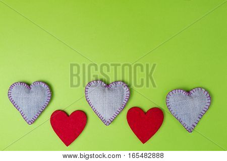 Valentine hearts of denim jeans and red felt on colourful greenery background. Top view. Copy space for text.