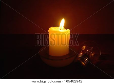 Burning candle and lamp on desktop in darkness (when electricity lost ). Broken electrical wires via storm.