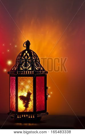 Fairy inside lantern illuminated by candle light with brilliant red and gold tones with glowing stars on outside/Fairy inside vintage Lantern lit by candlelight with a pattern of stars