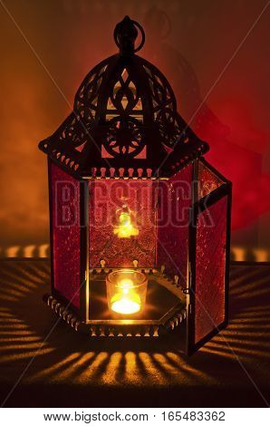 Metal Vintage Lantern illuminated by candle light with brilliant red and gold tones. Patterns of light spill all around it/Metal Vintage Lantern lit by candlelight with deep red and gold colors