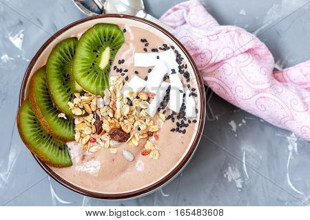 Chocolate smoothie bowl with kiwi and granola. Love for a healthy raw food concept.
