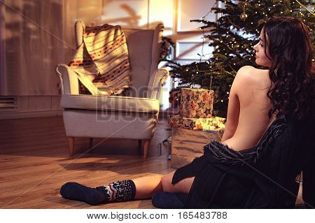 Innocent young brunet woman waiting a Christmas in room with christmas tree