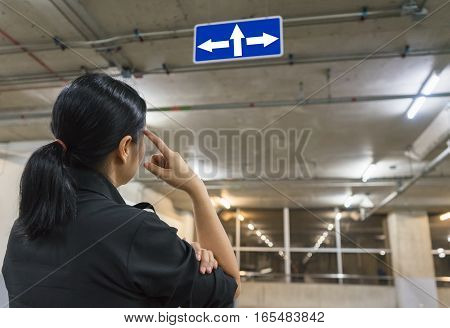 Asian woman thinking about the sign where to go