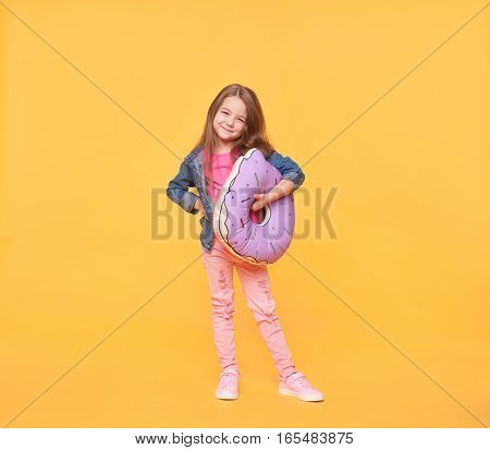 Smiling little girl holding a giant donut pillow in studio at yellow background. Full body size portrait of stylish preschooler wearing trendy clothes with original sleep pillow
