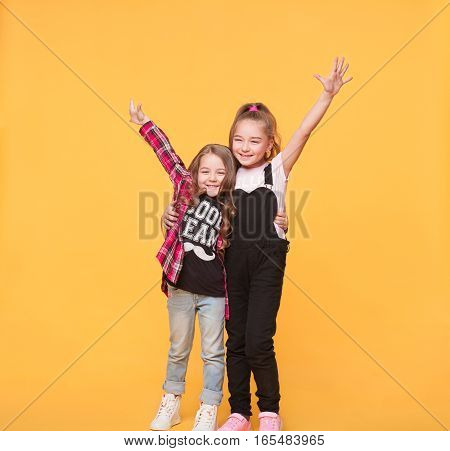 Studio portrait of two happy little girls embracing each other on yellow color background. Cheerful sister kids with hands raised isolated over colorful wall