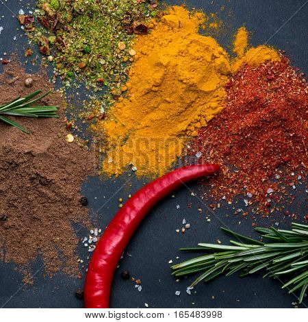 Various colorful herbs and spices on dark background