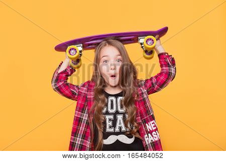 Shocked fashion kid concept - stylish little girl looking very surprised to the camera wearing casual clothes with skateboard isolated on yellow background
