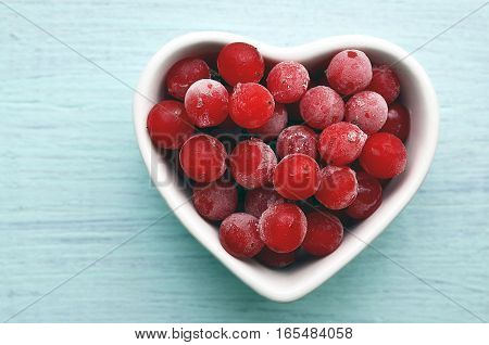 Frozen red viburnum berries in a white heart shaped bowl on a blue wooden background.Natural medicine,alternative treatment or health care concept.Selective focus.