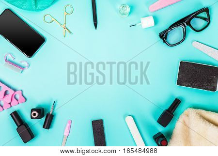 Top view of manicure and pedicure equipment on blue background. Still life. Copy space