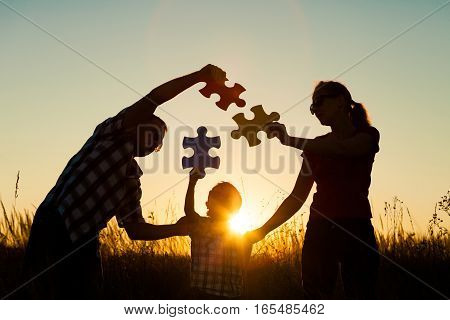 Happy Family Playing At The Park At The Sunset Time.