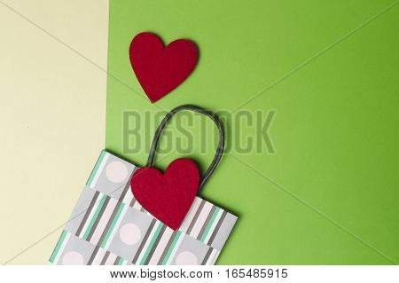Colorful shopping bag and two red hearts on greenery and yellow colored paper background. Top view. Flat lay. Copy space for text. Retail, sale, I love shopping concept