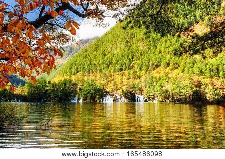 Scenic View Of Lake With Crystal Clear Water Among Fall Foliage