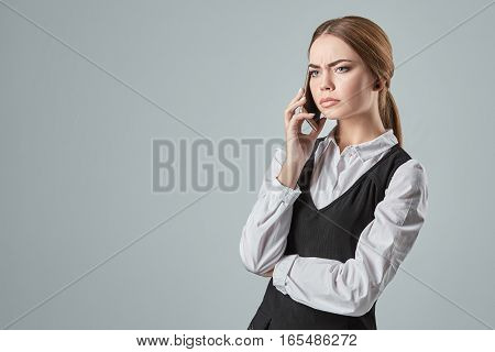 Young girl talking at the cellphone on a gray background. Emotions