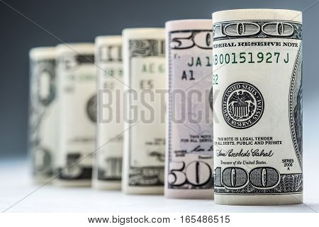 Dollar. Dollar banknotes roll in other positions. American US currency on white board and defocused background.