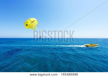 Photo of sea in protaras cyprus island with yellow parasailing with people and a boat immaculate blue water and sky