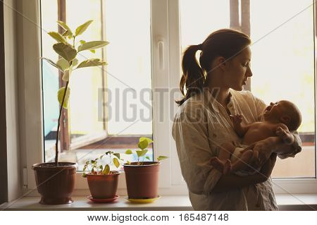 photo of young mother with baby at home