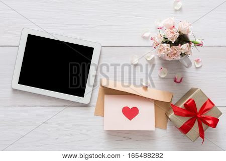 Valentine day internet e-mail concept, online connection holiday background. Tablet screen with copy space on white wood with rose flowers and letter, top view. Advertising mockup