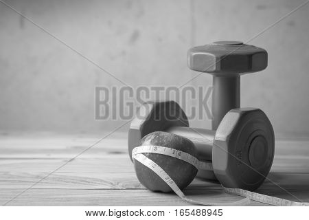 Apple And Measuring Tape And Pair Of Red 1 Kg Dumbbells On Wooden , Black And White
