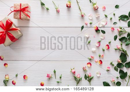 Valentine background with pink rose flowers frame and gift boxes with copy space on white rustic wood. Happy lovers day presents mockup
