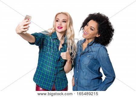 Two beautiful girls making selfie. Isolated on white background