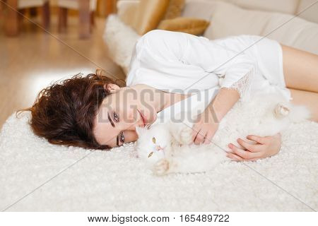 Cute Curly Girl In A White Silk Dressing Gown In The Early Morning Playing With White Fluffy Cat Sit