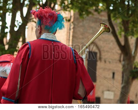 Performer Dressed in Red with Long Trumpet during Procession during Historical Event Reconstruction