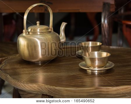 Traditional Asian Golden Teapot and Cups on Little Wooden Table