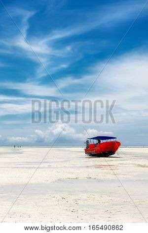 Red boat on the beach of Zanzibar on the blue sky background. Africa. Tanzania.