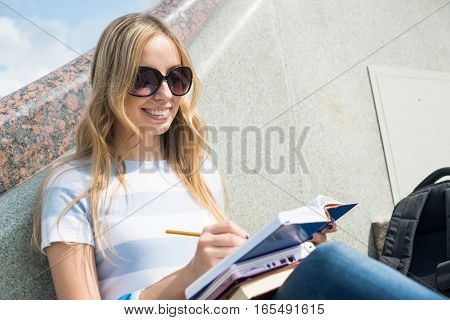 Smiling college student sitting on staircase and studying with books