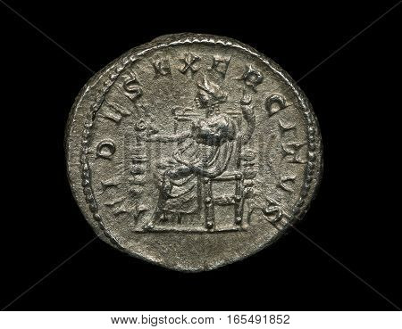 Ancient Roman Silver Coin With Figure Of Seated Person Isolated On Black