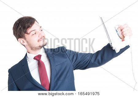 Man Wearing Suit Holding Iron And Looking At It